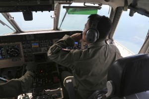 A crew member of an Indonesian Navy CN-235 airplane scans the horizon during a search operation for the missing AirAsia flight 8501 over the waters off Bangka Island, Indonesia, Tuesday. (AP Photo/Tatan Syuflana)