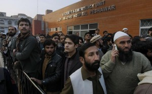 People gather at a hospital where victims of a Taliban attack are being treated in Peshawar, Pakistan, Tuesday. (AP Photo/Mohammad Sajjad)