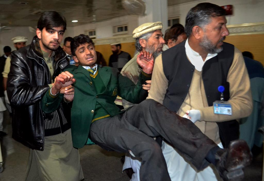 Volunteers and a medical worker carry a student, injured in the attack at a school by Taliban terrorists, at a local hospital in Peshawar, Pakistan, Tuesday. (AP Photo/Mohammad Sajjad)