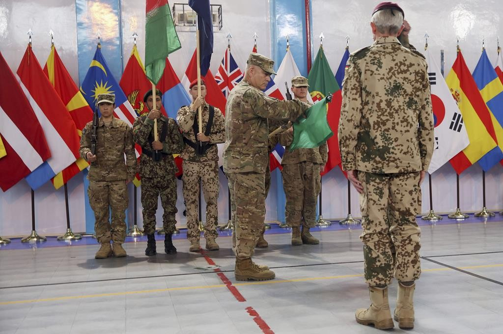 Commander of the International Security Assistance Force (ISAF), Gen. John Campbell, center, cases the ISAF flag during a ceremony at the ISAF headquarters in Kabul, Afghanistan, Sunday.  (AP Photo/Massoud Hossaini)