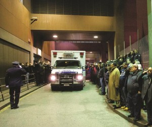 Mourners stand at attention as the bodies of two fallen NYPD police officers are transported from Woodhull Medical Center, Saturday, in New York.  (AP Photo/John Minchillo)