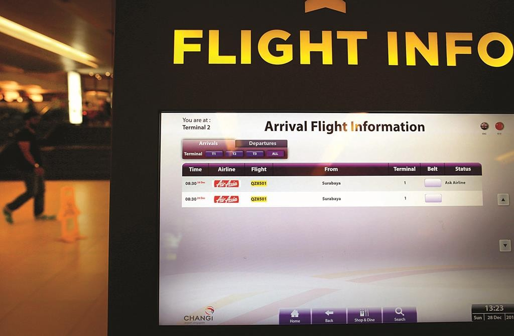 "An electronic kiosk providing flight information shows the status for AirAsia flight QZ8501 from Surabaya to Singapore as ""Ask Airline,"" Sunday.  (AP Photo/Wong Maye-E)"