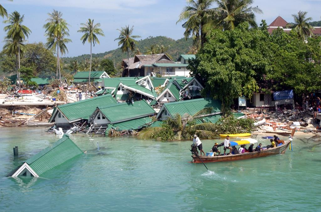 In this Dec. 28, 2004 file photo, a boat passes by a damaged hotel, at Ton Sai Bay on Phi Phi Island, in Thailand.  (AP Photo/Swuzanne Plunkett, File)