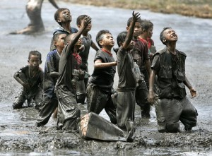 In this Monday, Jan. 17, 2005 file photo, refugee children try to catch relief goods tossed from an Australian military helicopter in a rice paddy in Lampaya, outskirts of Banda Aceh, Indonesia. (AP Photo/Eugene Hoshiko, File)