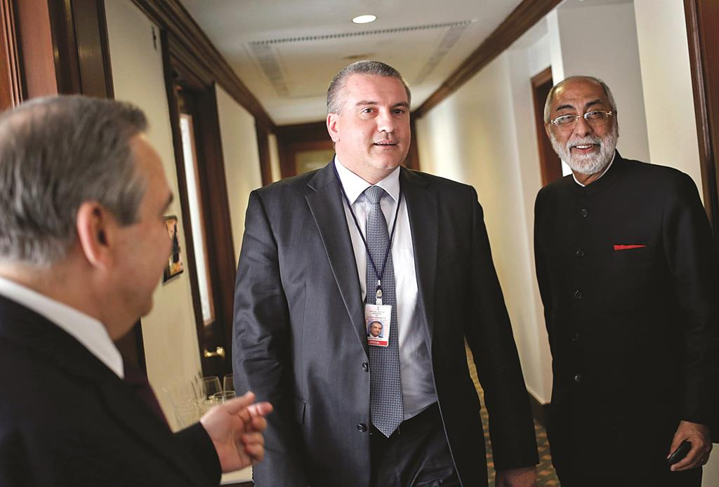 Sergey Aksyonov (C), the leader of Crimea, the former Ukrainian territory annexed by Russia, walks inside a hotel after having his lunch as Indian businessman Gul Kripalani (R) watches, in New Delhi on Thursday.  (REUTERS/Anindito Mukherjee)