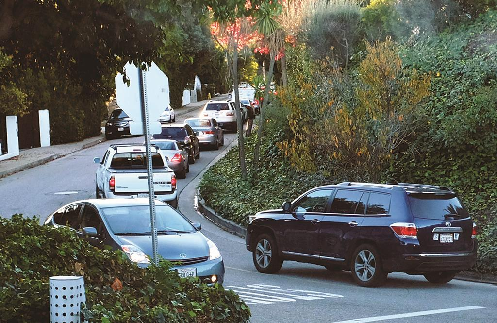 This Tuesday, Dec. 9, early morning rush hour traffic winds it's way along a narrow street in the Sherman Oaks section of Los Angeles. (AP Photo/Richard Vogel)