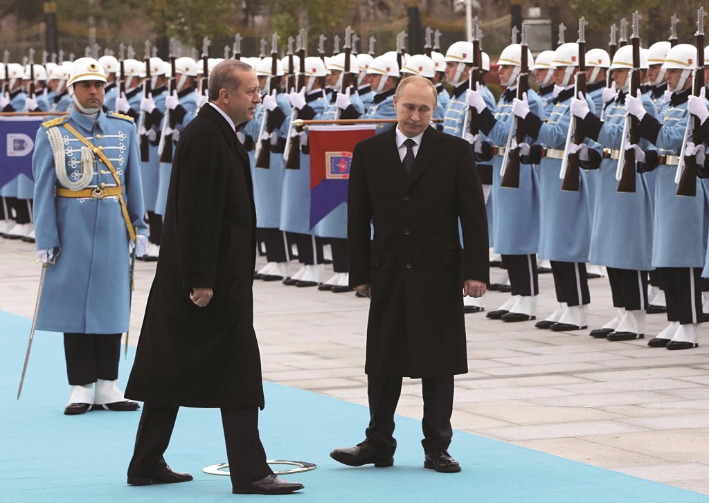 Russian President Vladimir Putin (R) and his Turkish counterpart Recep Tayyip Erdogan inspect a military honor guard during a welcome ceremony at the new Presidential Palace in Ankara, Turkey, Monday. (AP Photo/Burhan Ozbilici)