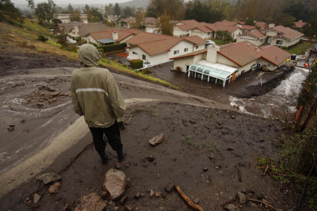 Camarillo city manager Bruce Feng watches as mud and debris flow behind a home that was red-tagged last month from a previous mudslide in Camarillo Springs. (Al Seib/Los Angeles Times/TNS)