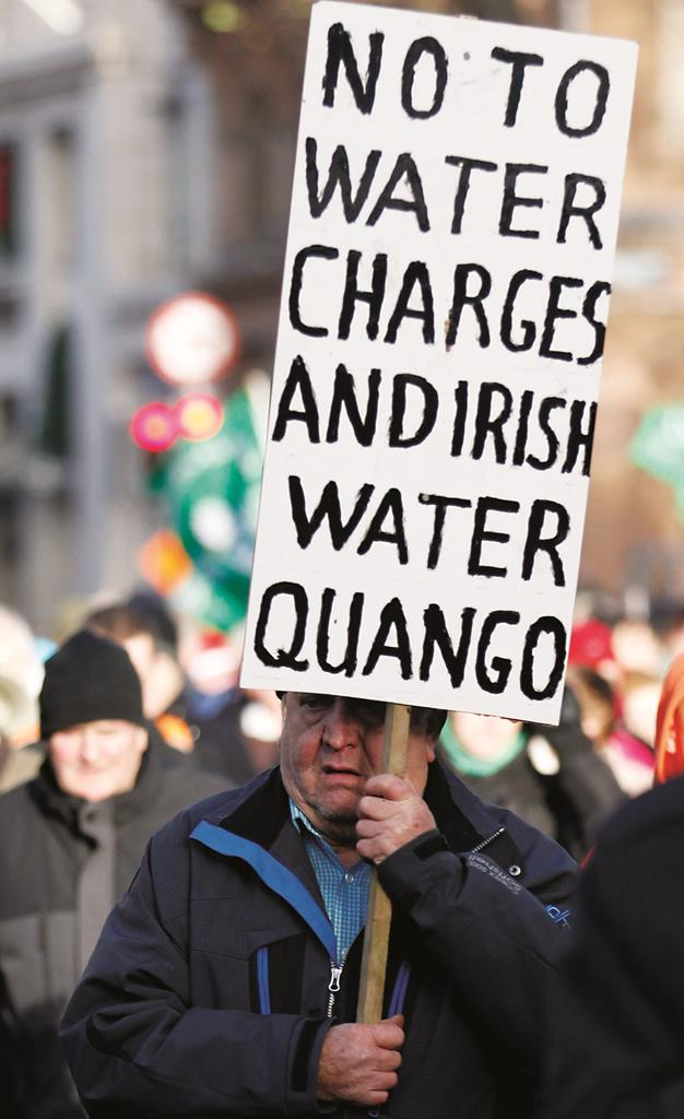 A water tax protester demonstrates close to government buildings in Dublin city center, Ireland, Wednesday. (AP Photo/Peter Morrison)