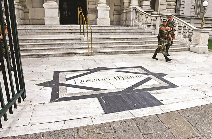 Two military officers leave the military hospital in Montevideo, Uruguay, Sunday. Uruguayan officials declined comment on the transfers but Adriana Ramos, a receptionist at the hospital, said the six men were being examined there.  (AP Photo/Matilde Campodonico)