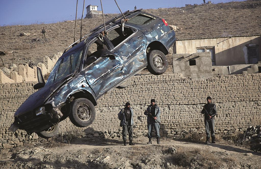 Afghan security force personnel look at a damaged civilian vehicle, being lifted to be removed from the site of a suicide attack in Kabul, Afghanistan Thursday. (AP Photo/Massoud Hossaini)