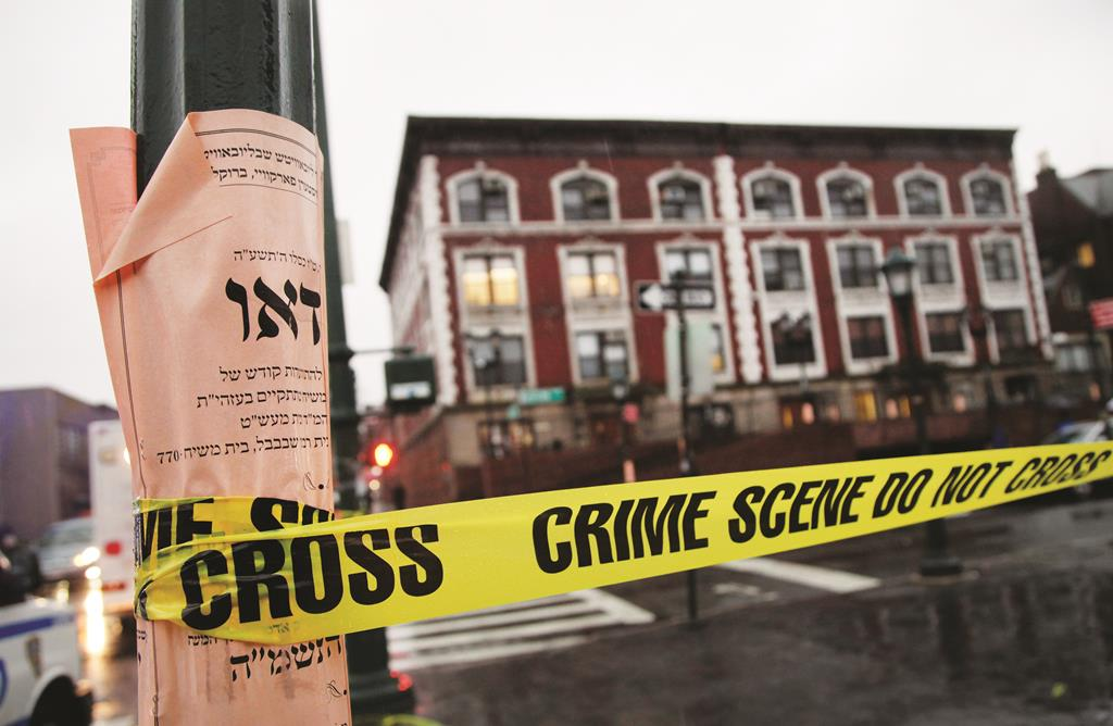 Crime scene tape is wrapped around a pole in front of Chabad-Lubavitch headquarters. (AP Photo/Mark Lennihan)
