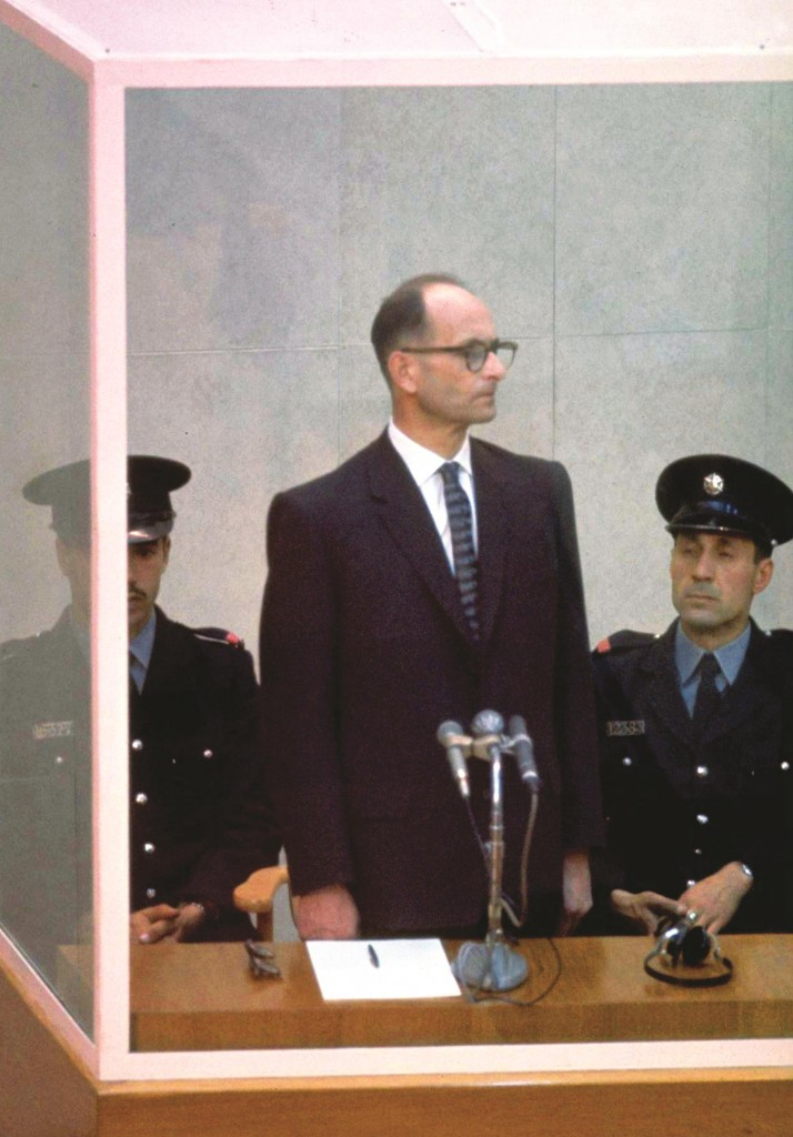 JERUSALEM, ISRAEL: (FILE PHOTO) Nazi war criminal Adolph Eichmann stands in a protective glass booth flanked by Israeli police during his trial April 21, 1961 in Jerusalem. The Israeli police donated Eichmann's original handprints, fingerprints and mugshot to Jerusalem's Yad Vashem Holocaust memorial ahead of Israel's annual Holocaust remembrance day May 4, 2005 which this year also marks the 60th anniversary of the Nazi's World War II defeat in 1945. (Photo by John Milli/GPO via Getty Images)