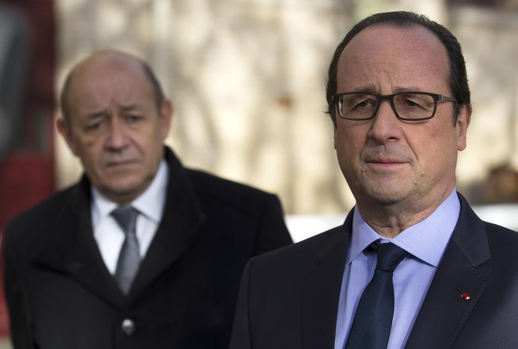 French President Francois Hollande (R), flanked by Defense Minister Jean-Yves Le Drian, addresses media as part of his tour of the the Quartier des Celestins, the barracks housing the Republic Guard, in Paris, France, Tuesday. (AP Photo/Ian Langsdon, Pool)