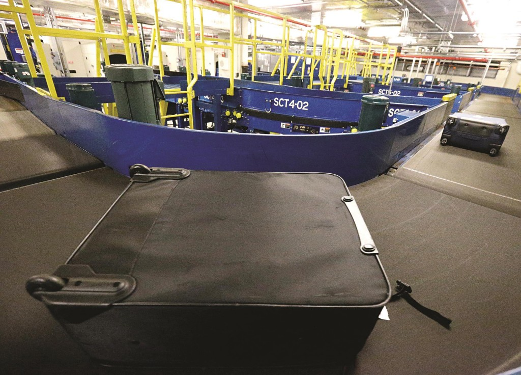 A traveler's bag runs on a rail at a security checkpoint area at Midway International Airport, Friday, in Chicago. (AP Photo/Nam Y. Huh)