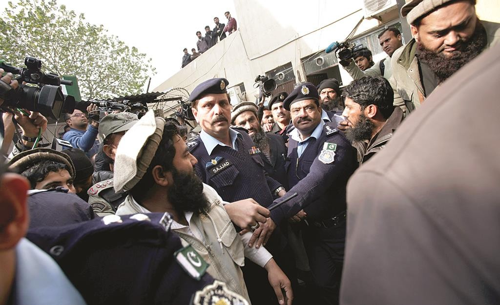 Pakistani police officers make way for Zaki-ur-Rahman Lakhvi, center in light brown cap, the main suspect in the Mumbai terror attacks in 2008, after his court appearance in Islamabad, Pakistan, Tuesday. (AP Photo/Anjum Naveed)