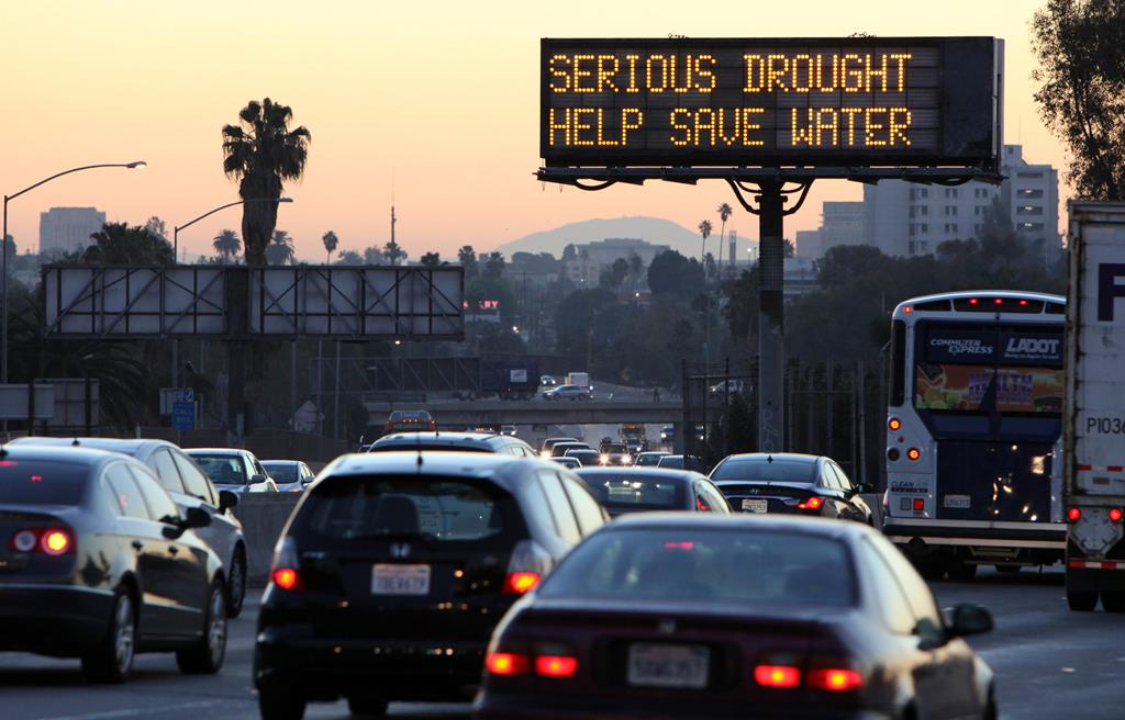 Morning traffic makes its way toward downtown Los Angeles along the Hollywood Freeway, past an electronic sign warning of severe drought.  (AP Photo/Richard Vogel)