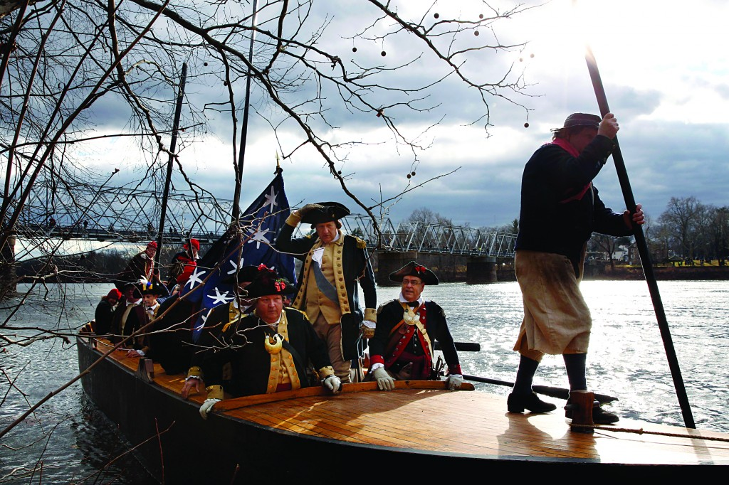 George Washington, played by John Godzieba, standing center, holds onto his hat as he and his troops land in Titusville, N.J., after crossing the Delaware River during the 62nd annual reenactment of Washington's daring 1776 crossing of the river — the trek that turned the tide of the Revolutionary War — on Thursday, in Washington Crossing, Pennsylvania. (AP Photo/Mel Evans)