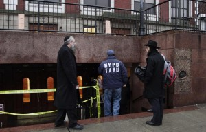 "Police keep guard outside the ""770"" complex after the attack. (AP Photo/Mark Lennihan)"