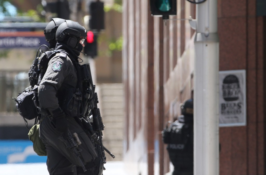 Police run past a cafe under siege at Martin Place in the central business district of Sydney, Australia, Monday (Australian time.)  (AP Photo/Rob Griffith)