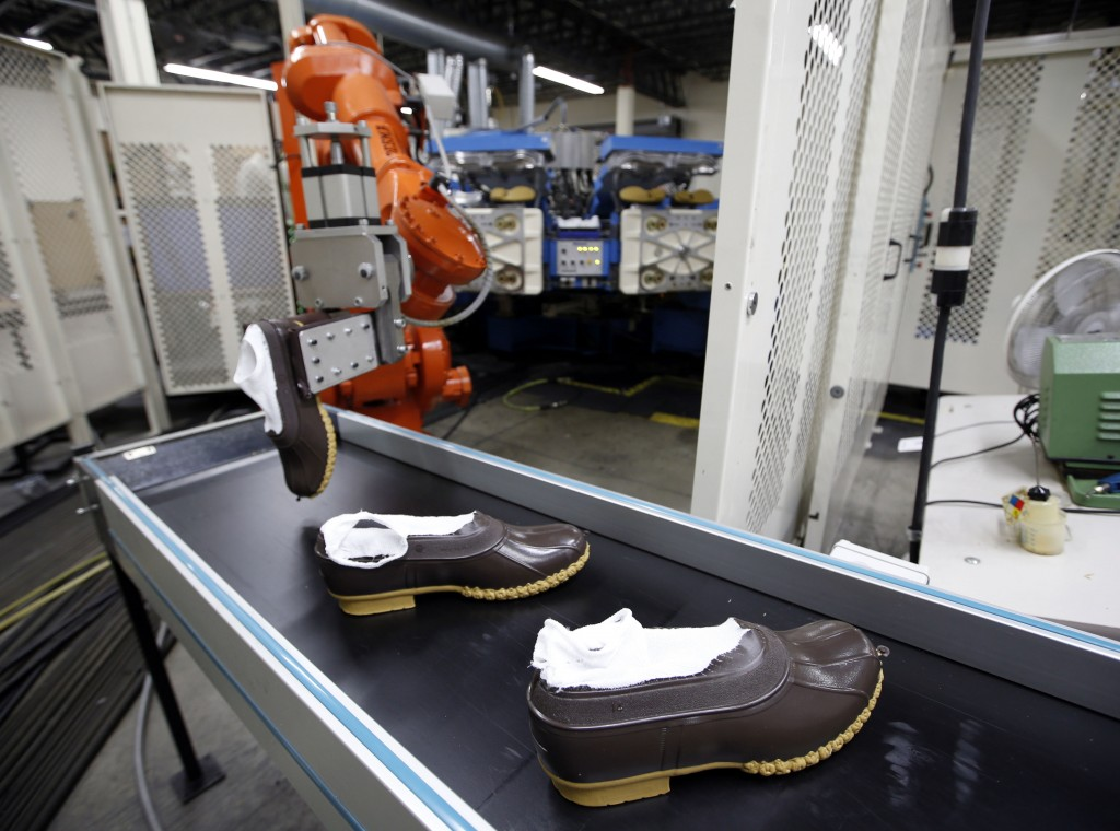 In this Tuesday, Dec. 2, 2014 photo, rubber bottoms of future L.L. Bean boots are dropped onto a conveyor belt by a robotic arm after the sole came out of a molding machine at a facility in Lewiston, Maine. (AP Photo/Robert F. Bukaty)