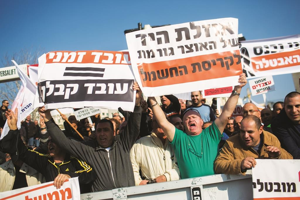 Employees of the Israeli Electrical Company protesting outside the prime minister's office in Yerushalayim. (Yonatan Sindel/Flash90)