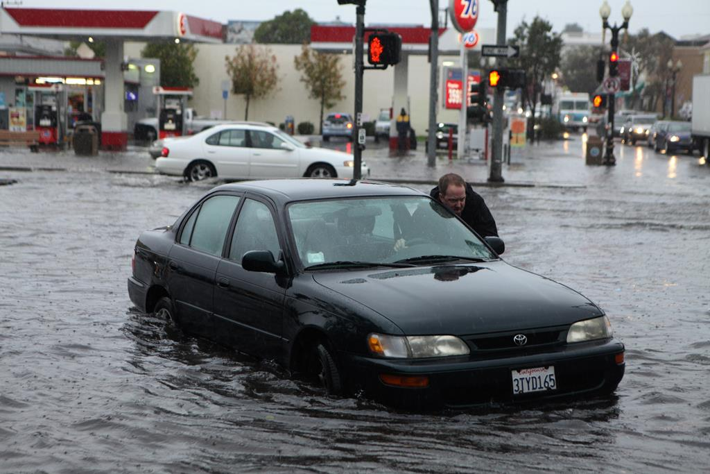 Mark Kunze of San Bruno pushes his stalled vehicle out of the flooded intersection of Airport Blvd. and Grand Ave. in South San Francisco, on Thursday. (AP Photo/Alex Washburn)