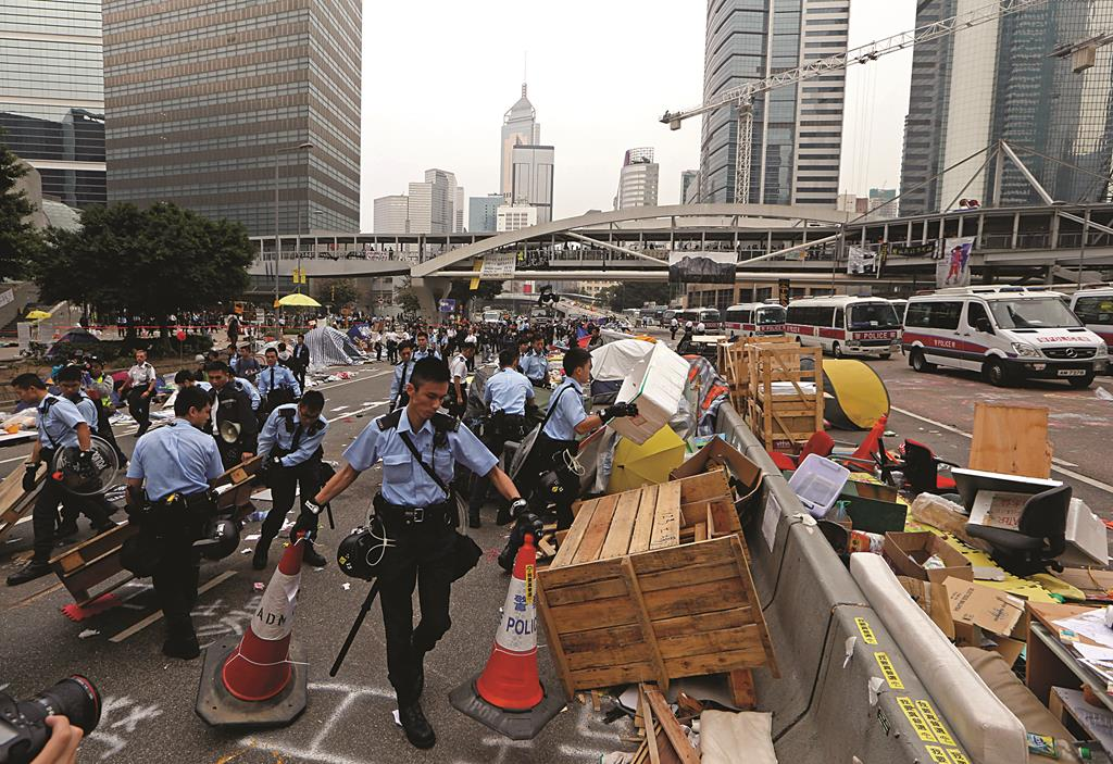 Police officers clear away protesters' belongings from outside government buildings in Hong Kong, Thursday. (AP Photo/Kin Cheung)