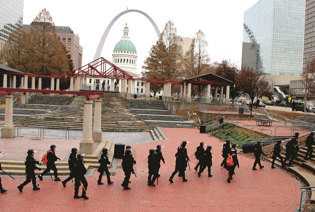 Officers wearing riot gear walk through a park in downtown St. Louis. President Obama wants more police to wear cameras to record events like the shooting death of Michael Brown. (AP Photo/Tom Gannam)
