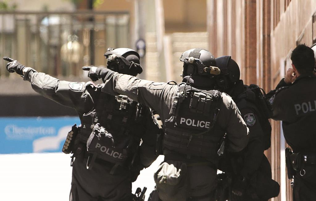 Armed police officers point as they stand at the ready near the Lindt Cafe, which was held under siege for 16 hours in Sydney, Australia, Monday. (AP Photo/Rob Griffith)
