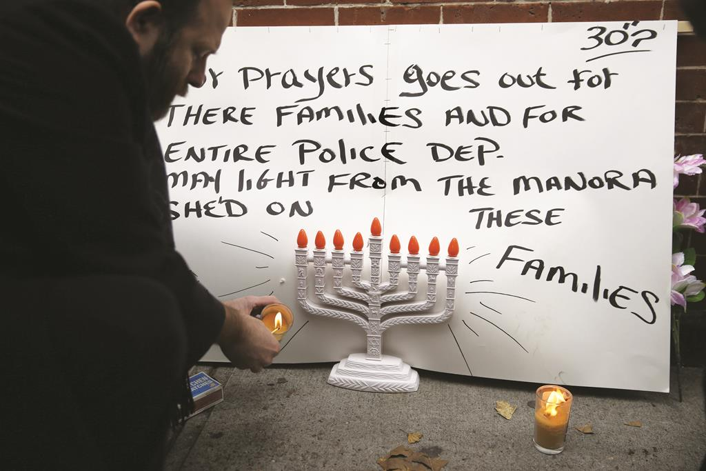 Police Department A Brooklyn resident lights candles and leaves a poster at an impromptu memorial near the site where two police officers were killed in Brooklyn, Sunday.  (AP Photo/Seth Wenig - AP Photo/New York)