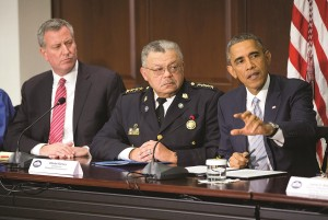 President Barack Obama (R) speaks at his meeting with elected officials, law enforcement officials and community and faith leaders in the Old Executive Office Building on the White House Complex in Washington, Monday. Obama said he wants to build better trust between police and the communities they serve. Also at the meeting are NYC Mayor Bill de Blasio (L) and Charles Ramsey (C) Commissioner of the Philadelphia Police Dept. (AP Photo/Pablo Martinez Monsivais)