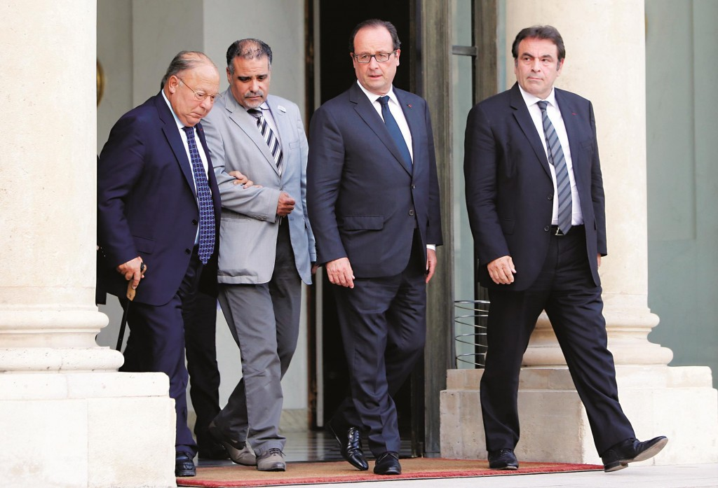 This Monday, July 21, 2014, photo shows French President, Francois Hollande (C), with Paris Mosque rector Dalil Boubakeur (L), and France's Jewish central Consistory president, Joel Mergui (R) after their meeting with representatives of Religions in France at the Elysee Palace in Paris, France.  (AP Photo/Francois Mori, File)