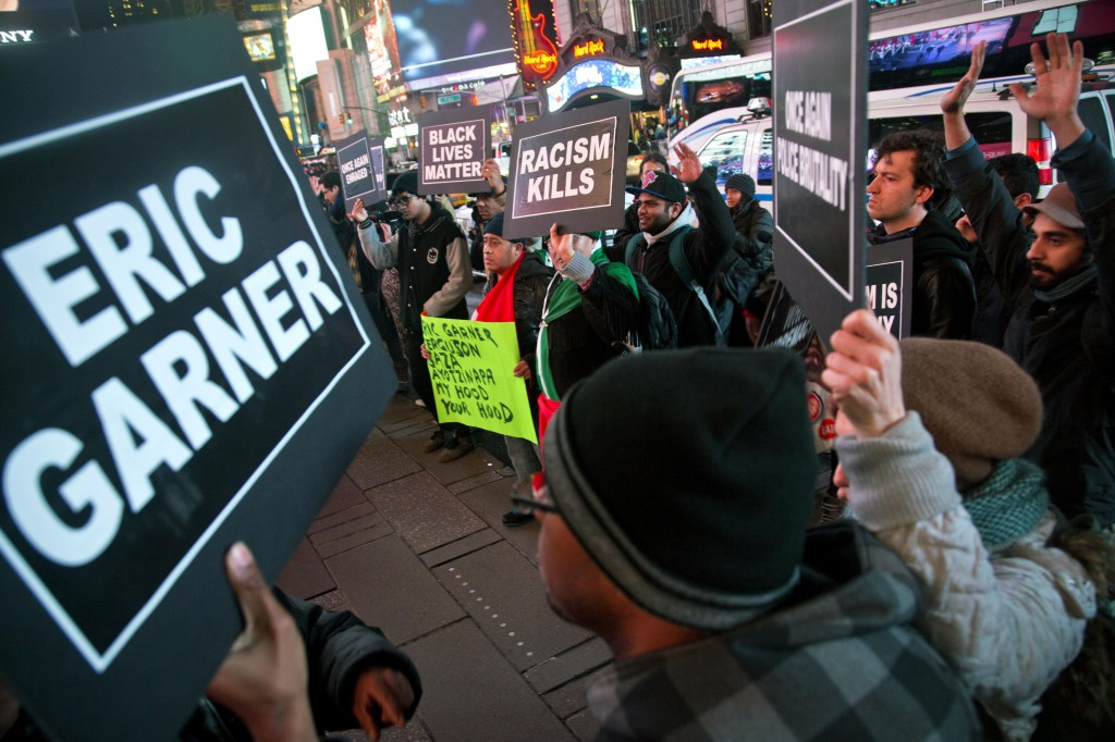 Protesters in Times Square raise their hands and chant while carrying signs in reaction to a non-indictment against a police officer in the death of Eric Garner, on Wednesday in New York City.  (AP Photo/Bebeto Matthews)