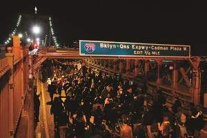 A group of protesters marches across the eastbound traffic lanes of the Brooklyn Bridge in the early morning hours of Thursday. (AP Photo/Jason DeCrow)