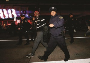 A protester is taken into custody early Thursday morning. (AP Photo/Julio Cortez)