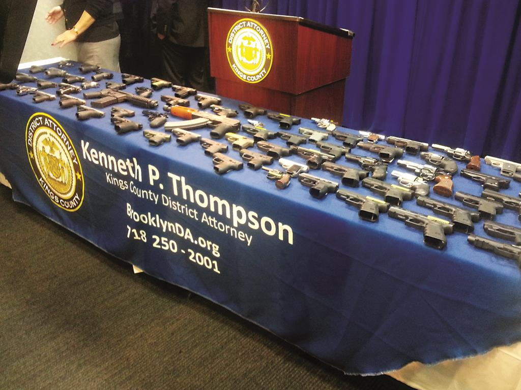 A collection of handguns and two assault rifles on Tuesday fill a table during a news conference at the Brooklyn DA's office. (AP Photo/Brooklyn DA, Christina Carrega-Woodby)