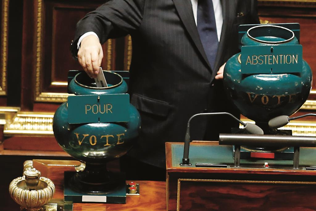 A French senator casts his ballot in an urn supporting a motion, at left, during a vote on the recognition of a Palestinian state, at the French Senate in Paris, France, Thursday. (AP Photo/Francois Mori)