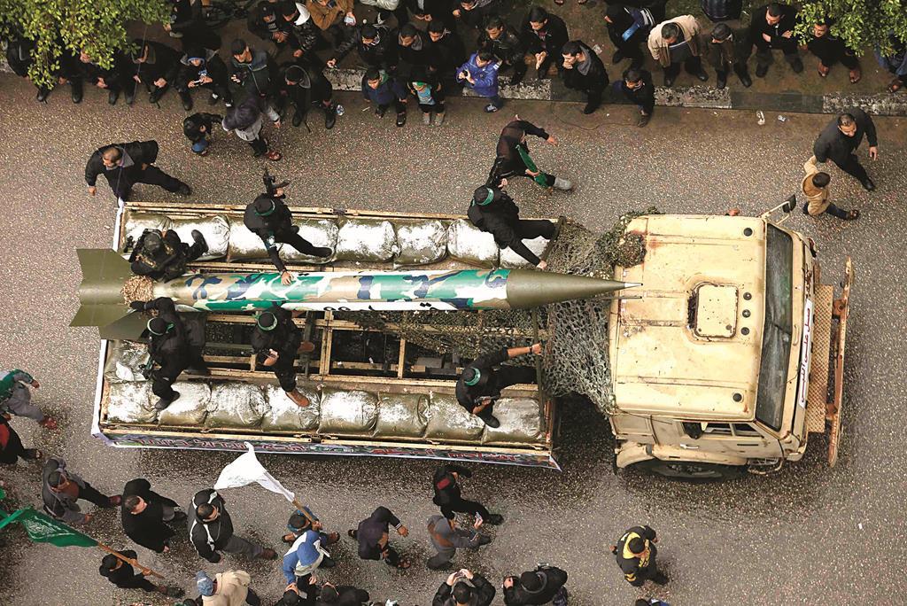 Palestinian members of al-Qassam Brigades, the armed wing of the Hamas movement, display a home-made rocket during a military parade marking the 27th anniversary of Hamas' founding, in Gaza City December 14, 2014. REUTERS/Suhaib Salem (GAZA - Tags: POLITICS MILITARY ANNIVERSARY) (Newscom TagID: rtrlsix788655.jpg) [Photo via Newscom]