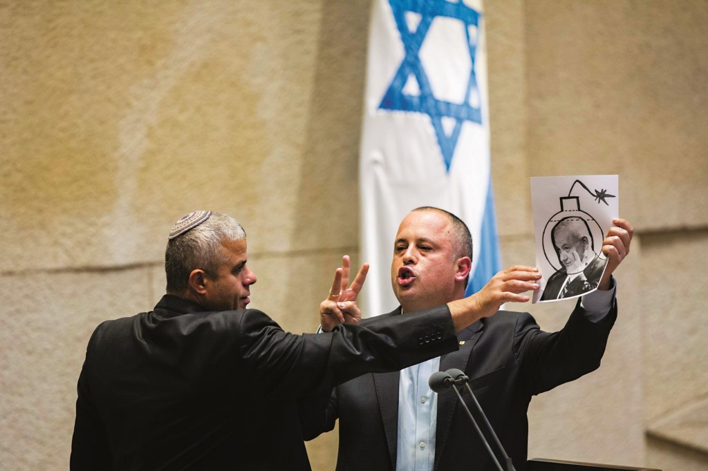 A Knesset security guard tries to grab a picture of Netanyahu as a ticking bomb away from Labor MK Hilik Bar in the plenum on Wednesday. (Yonatan Sindel/Flash90)