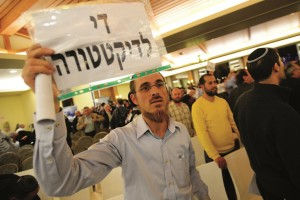 "A participant at the Likud party conference carries a sign reading ""enough of dictatorship,"" expressing dissatisfaction with Netanyahu's dominance of the party, in Ariel on Tuesday night. (Gili Yaari/Flash90)"