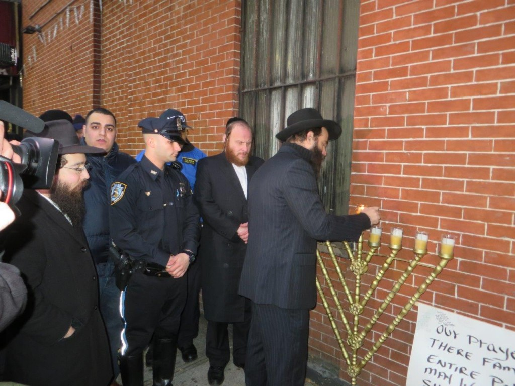 Lighting the menorah at the site where the two police officers were shot to death on Saturday. (JDN)