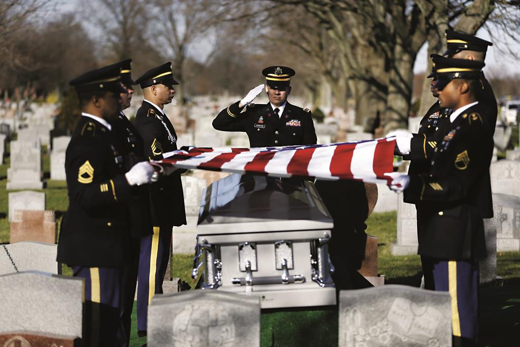 A soldier on Monday salutes during a graveside service for Anthony La Rossa (bottom right) in Farmingdale, N.Y. (AP Photo/La Rosa Family Photo - Seth Wenig)
