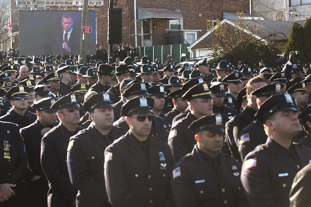 Police officers turn their backs as Mayor Bill de Blasio speaks on Saturday at the funeral of Officer Rafael Ramos in Queens. (AP Photos)