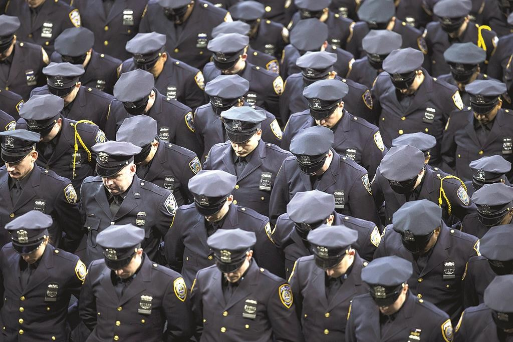 New recruits bow their heads Monday in honor of the two murdered police officers, during an NYPD graduation ceremony at Madison Square Garden. (AP Photo/John Minchillo)