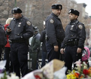 Police officers on Monday stand at the scene in Bedford-Stuyvesant where two officers were killed. (AP Photo/John Minchillo)