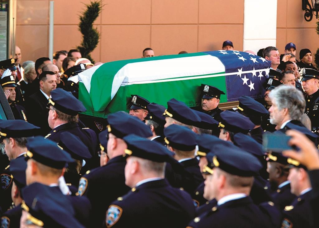 The casket draped in an NYPD flag is escorted Saturday by an NYPD honor guard.