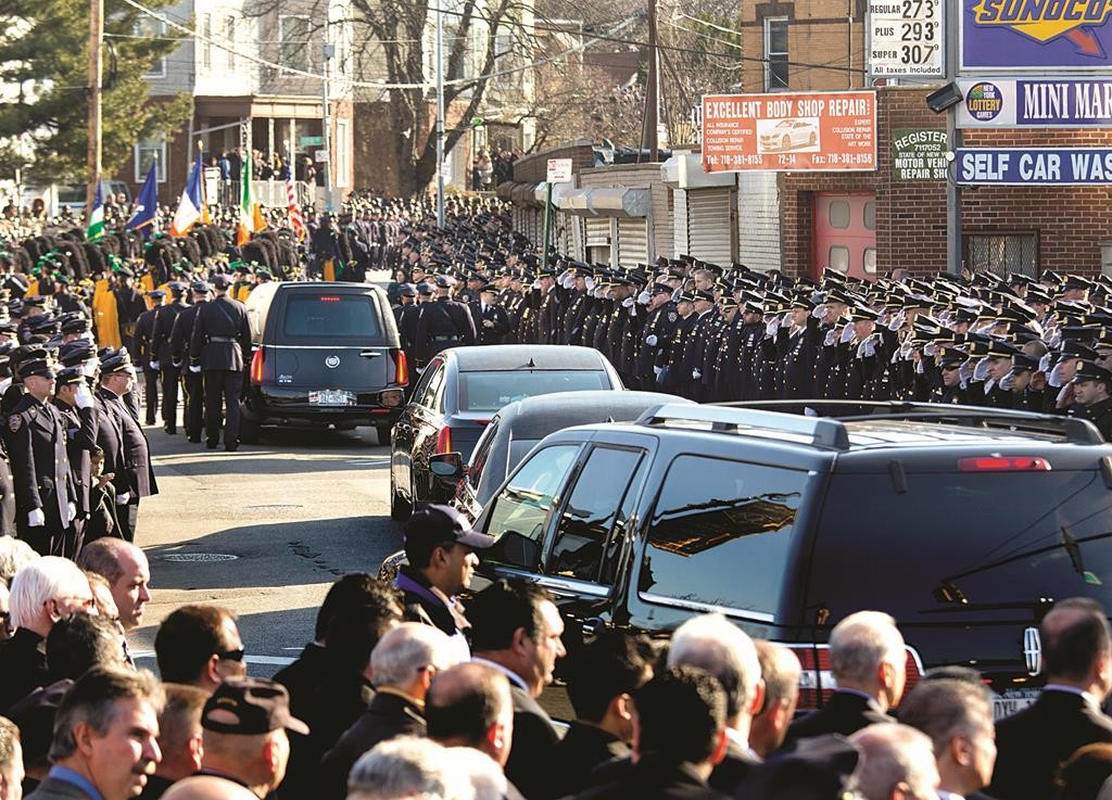 Thousands of police officers salute as the hearse passes by after the funeral.
