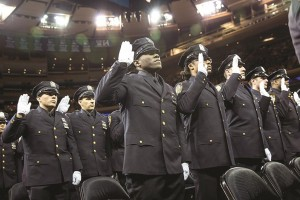 Police officers recite an oath during a graduation ceremony at Madison Square Garden. (Andrew Burton/Getty Images)