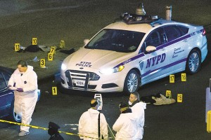 Bulletproof vests lie on each side of an NYPD patrol car as investigators work at the murder scene. (AP Photo/John Minchillo)